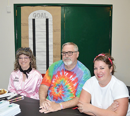 From left to right is Nilla Fuller, Board President Steve Larsgaard and Family Nurse Practitioner Abby Burkhart of Agape Hospice and Palliative Care by the goal poster at the 1950s-themed sock hop given to thank the community.