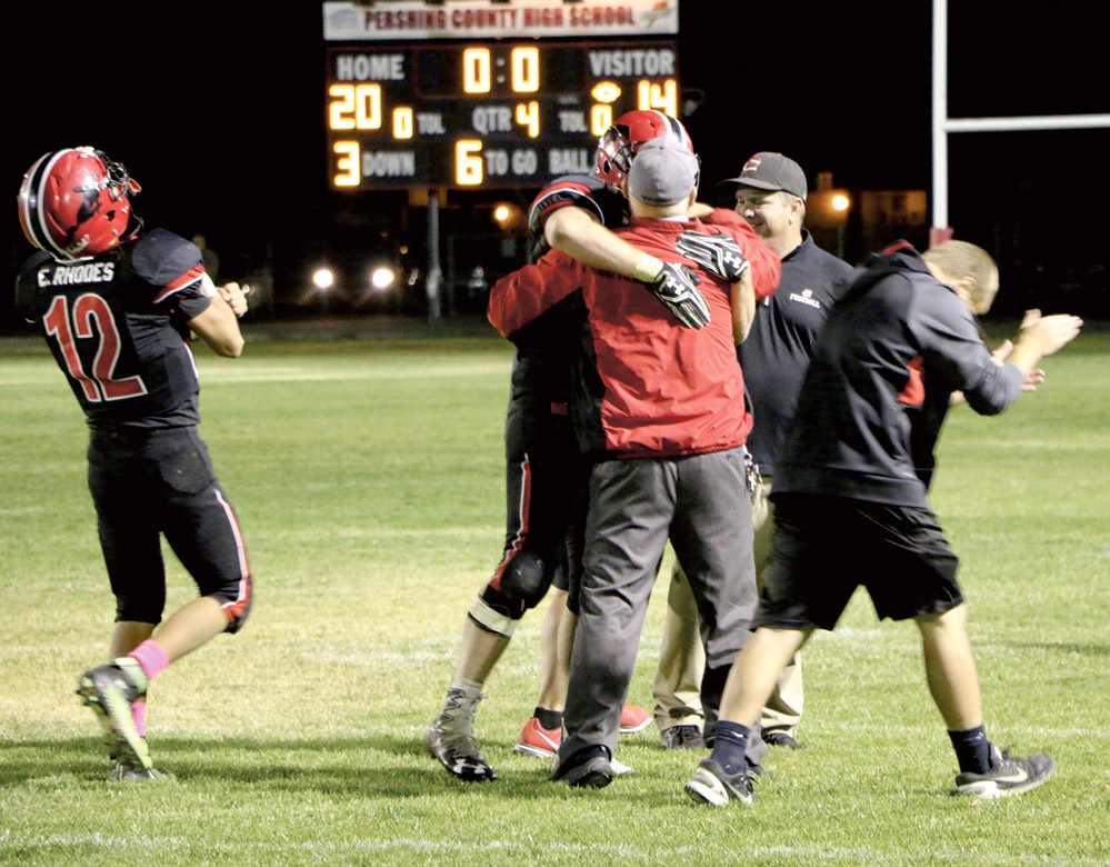Ethan Rhodes (left) and Mike Brooks react to the score board while Tom Brooks hugs Ty Arnett and Dave McLean smiles after Pershing County beat Yerington 20-14 on Friday, in Lovelock. The win ended the Lions 29-game winning streak.